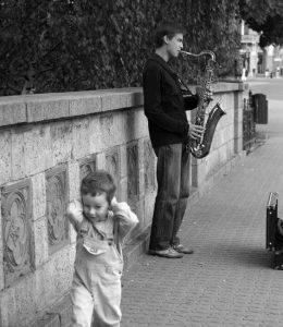 Katusoittaja soittaa saksofonia, lapsi pakenee korviaan pidellen. Kevennys.